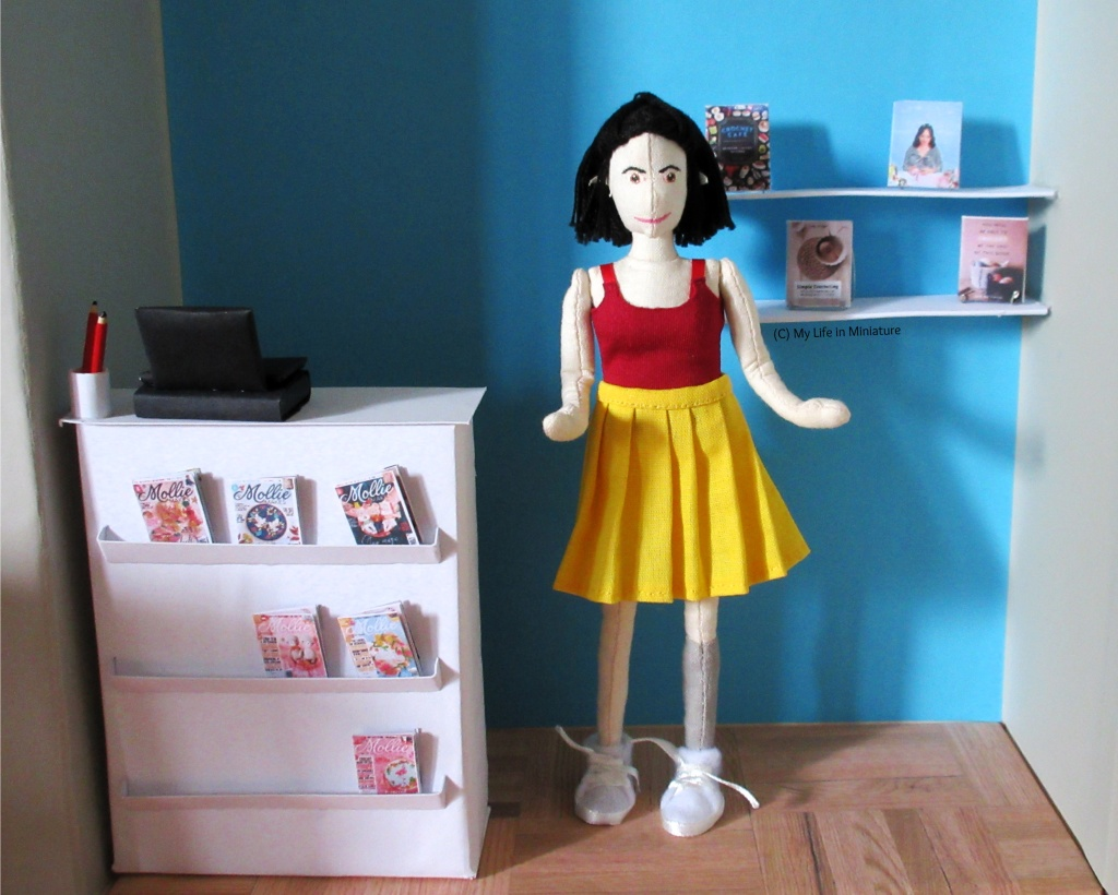Tiffany stands in the middle of the frame. To her left is the counter and to her right are two shelves attached to the blue wall behind her. There are four craft books on the shelves, displayed on stands.