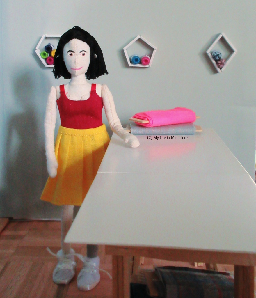 Tiffany stands to the left of the fabric table, one hand resting on the surface. A bolt of grey and a bolt of pink fabric are on the table. Behind her are three shelves shaped like hexagons, diamonds, and pentagons, all holding balls of yarn.