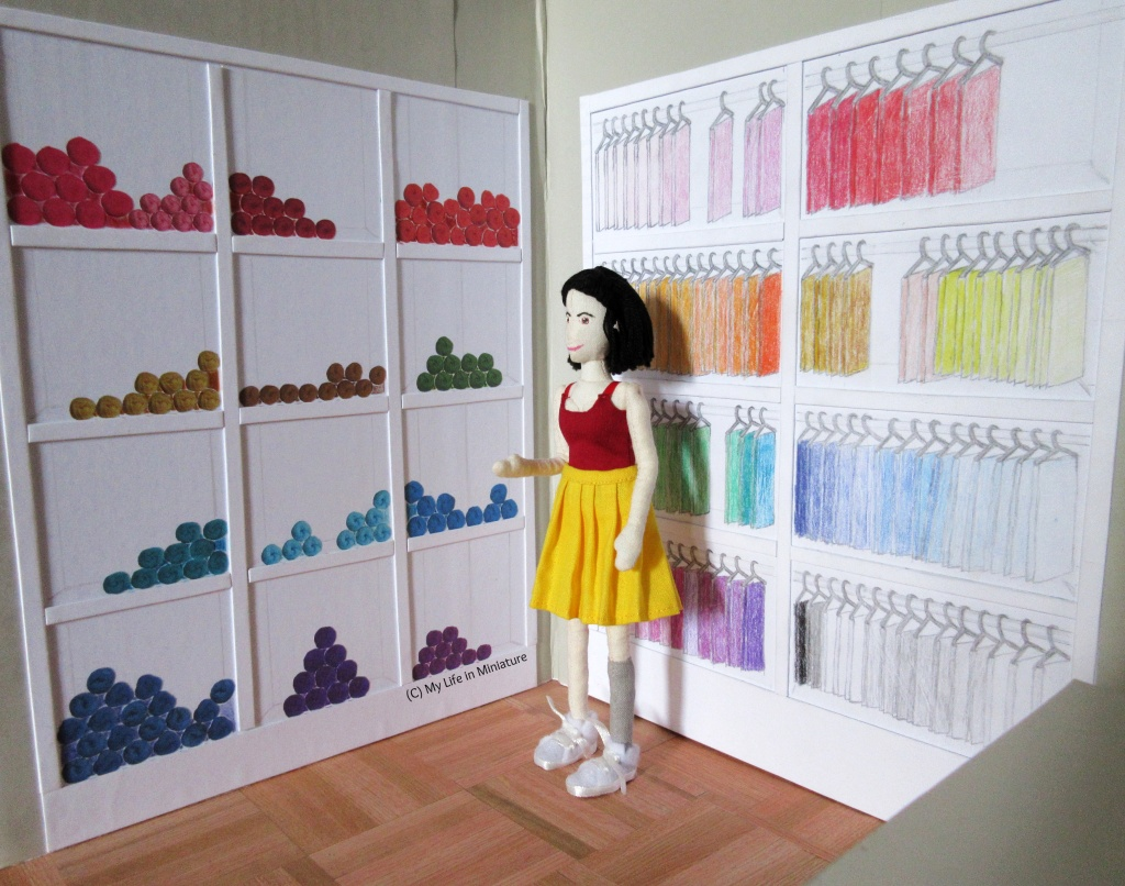 Tiffany stands in the corner between two large white shelving units. The unit on her left holds a rainbow of yarn balls, and the ight-hand one holds racks of hanging fat quarters, arranged by colour.