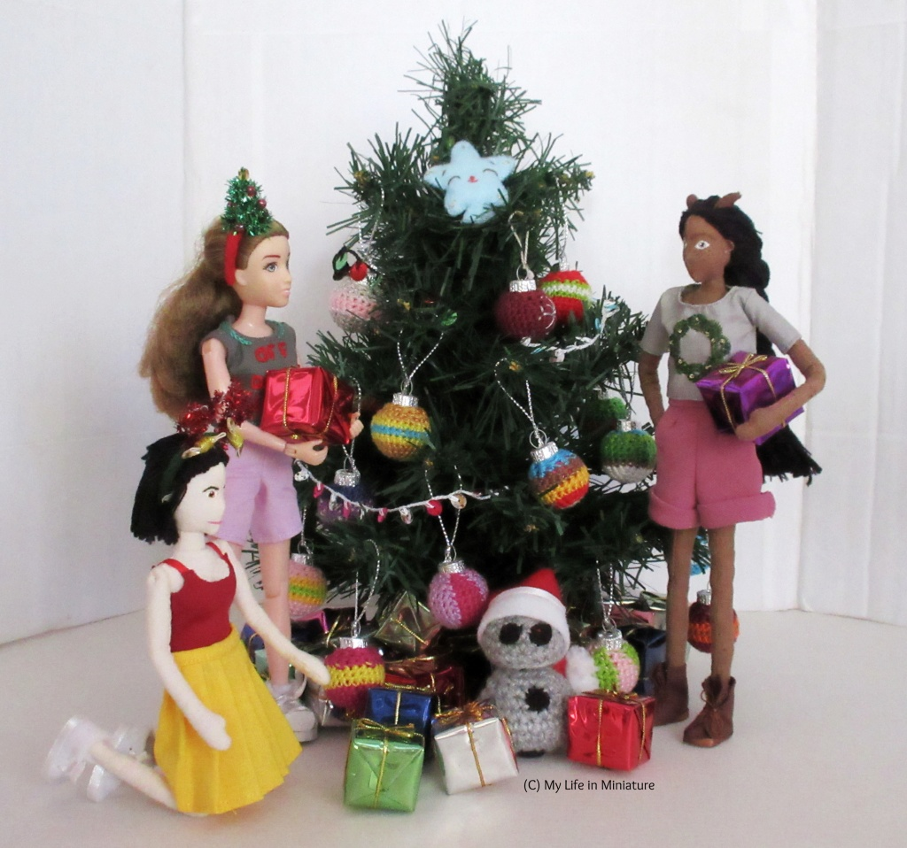 Sarah, Tiffany, Petra and Chip are around the Christmas tree. Sarah and Petra hold presents and stand on either side of the tree, looking at each other. Tiffany is kneeling beside Sarah, reaching for a present in front of Chip, who is underneath the tree amongst a lot of presents. Everyone is wearing festive t-shirts and headbands.