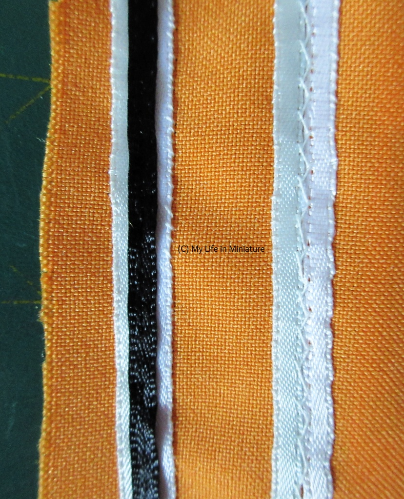 Overhead shot of two stripes in progress. The stripe on the right has a strip of pale blue ribbon sewn next to a strip of white ribbon. They are herringbone stitched together down the centre. The stripe on the left is complete, with the black ribbon back-stitched down the centre.