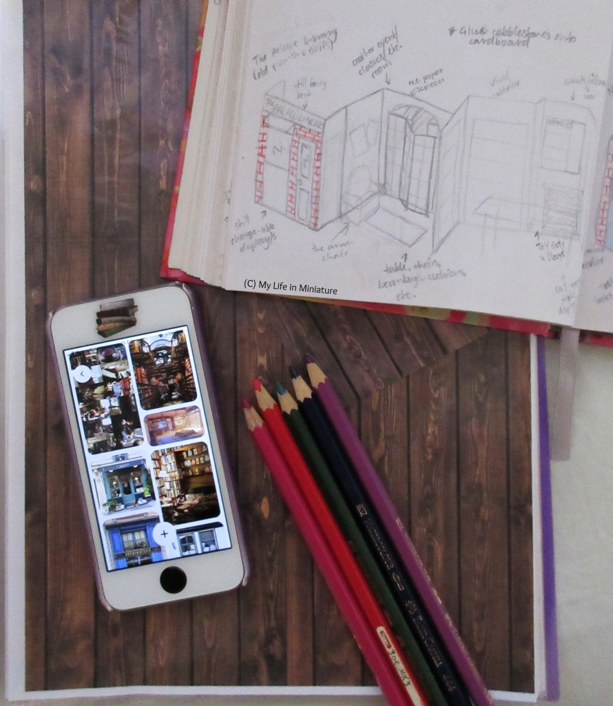 The corner of a sketchbook, five coloured pencils, and a phone sit on top of an open folder. The folder is open to a piece of paper with dark wood printed on, in a clear plastic sleeve. The sketchbook shows plans for a bookshop. The phone is open to a Pinterest board with various bookshop images on.