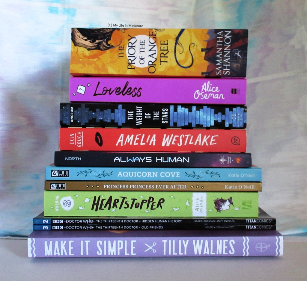 A stack of books sits in front of a white background. Top to bottom, the books are: 'The Priory of the Orange Tree' by Samantha Shannon; 'Loveless' by Alice Oseman; 'The Weight of the Stars'  by K. Ancrum; and 'Amelia Westlake'  by Erin Gough. The graphic novels are: 'Always Human' by Ari North; 'Aquicorn Cove' and 'Princess Princess Ever After' by Kay O'Neill; Heartstopper vol. 3 by Alice Oseman, the Thirteenth Doctor comics vol. 2 and 3 from Titan Comics. At the bottom is 'Make it Simple' by Tilly Walnes.