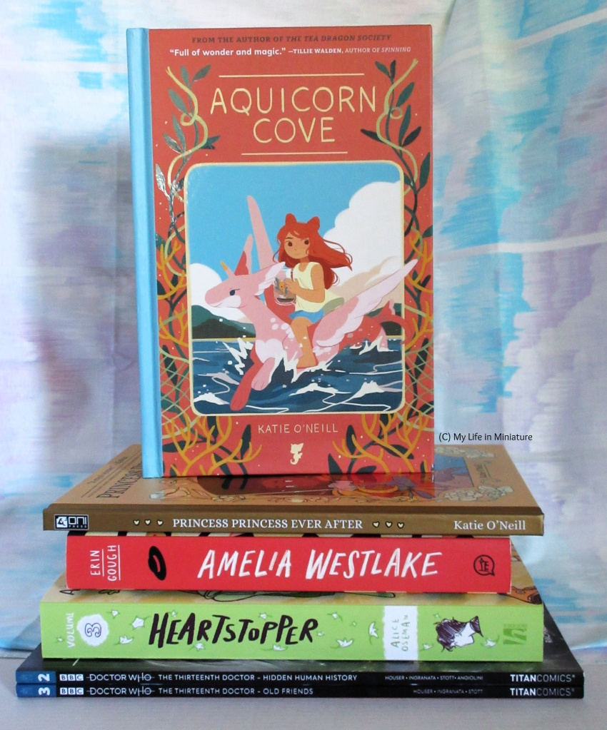 'Aquicorn Cove', 'Princess Princess Ever After', 'Amelia Westlake', Heartstopper vol. 3 and the two Thirteenth Doctor comics sit in a pile. 'Aquicorn Cove' is standing on top so the cover is visible.