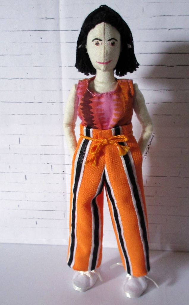 Tiffany stands in front of a white brick background, looking at the camera. She wears a t-shirt and a pair of bright orange pants. The pants have vertical black stripes which are sandwiched in-between pale blue and white stripes. They also have an orange plaited cord tied around the waist and pockets.