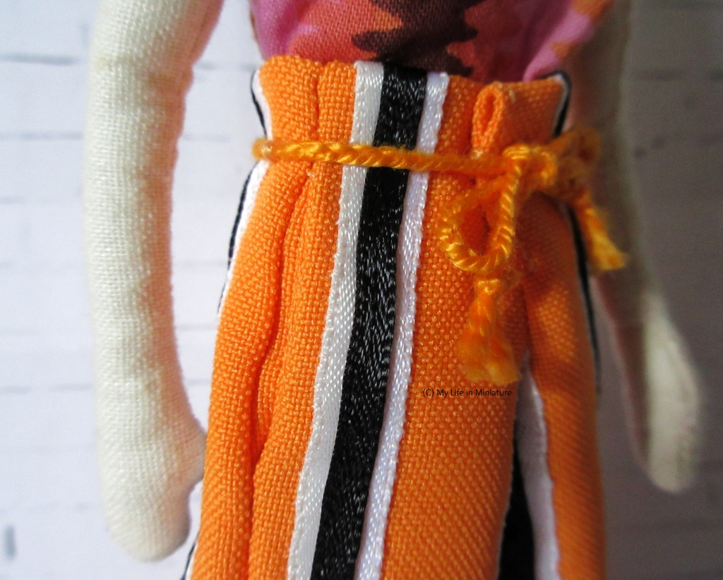 Detail shot of the plaited waist tie, the stripes, and the side seam pocket opening.