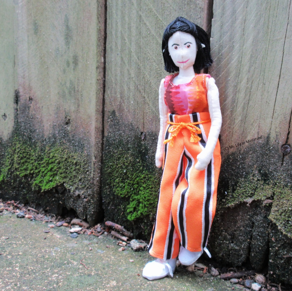 Tiffany leans against a wooden fence, one foot up against the wood, wearing the orange striped pants. There is green moss along the base of the fence, and she is looking at the camera.