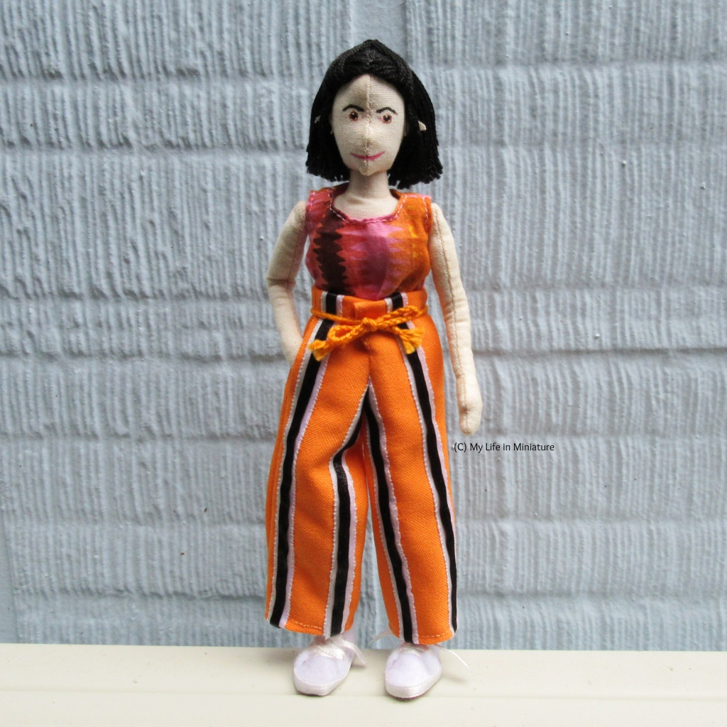 Tiffany stands against a pale blue textured wall, looking at the camera. She wears the orange striped pants, one hand in a pocket.