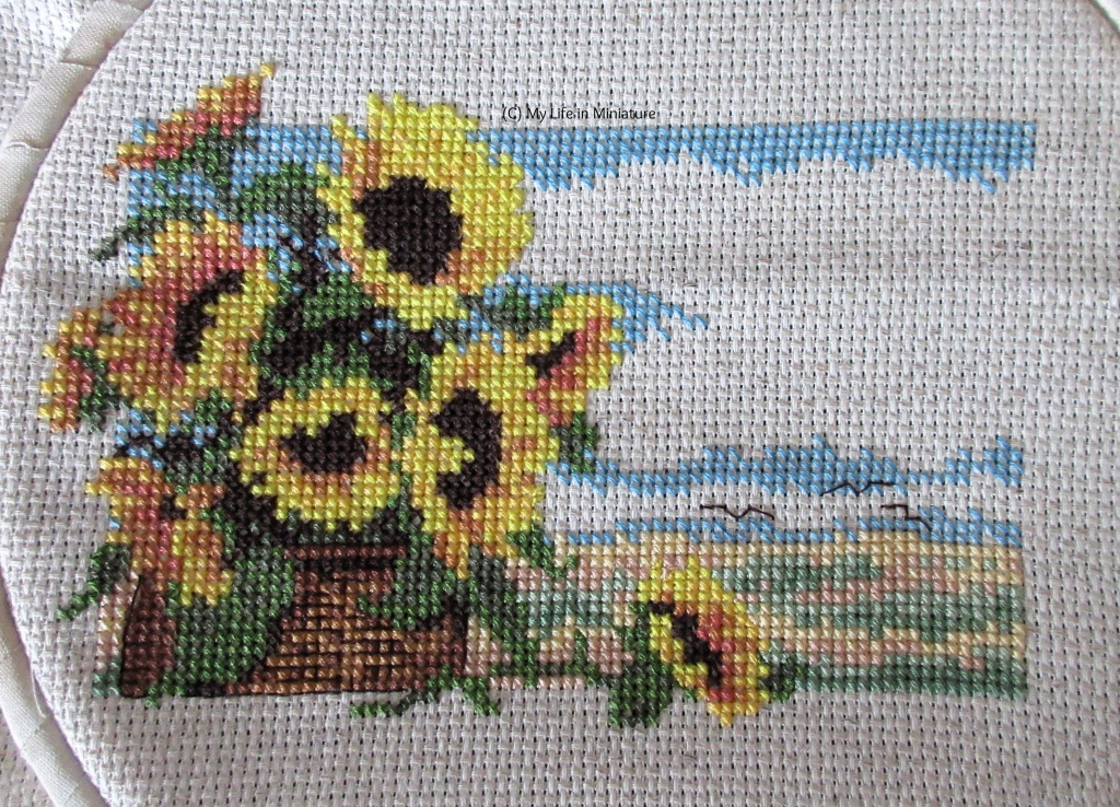 Nine sunflowers in a basket against a serene countryside are cross-stitched onto cream fabric. There are three birds backstitched in the sky and the basket has backstitched detail.