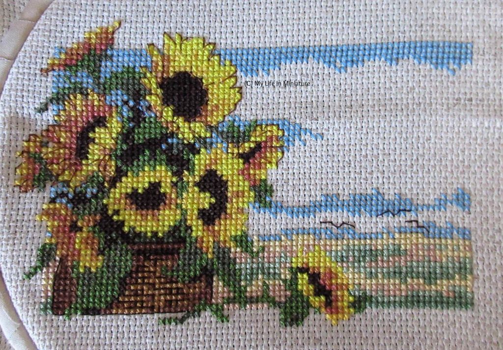 Nine sunflowers in a basket against a serene countryside are cross-stitched onto cream fabric. Four of the nine sunflowers are outlined, in addition to the basket and birds from last image.