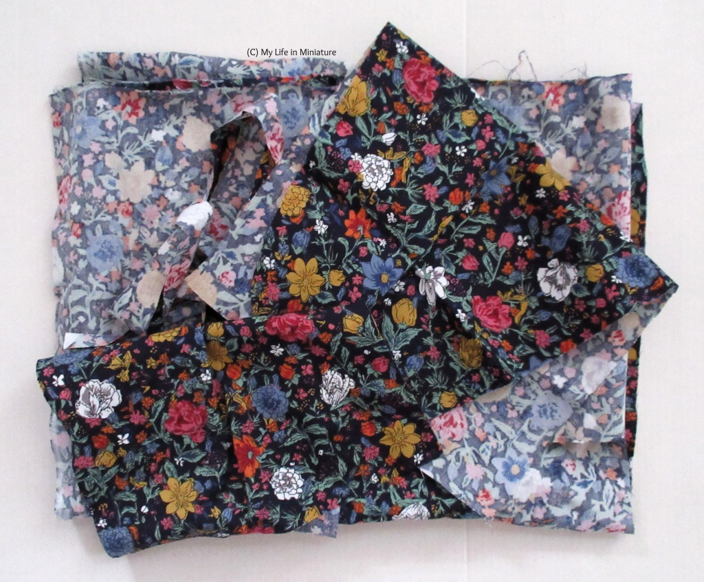 A folded pie of fabric scraps sits on a white background. The fabric is black with flowers and leaves printed on in green, blue, mustard yellow, pink, and white.