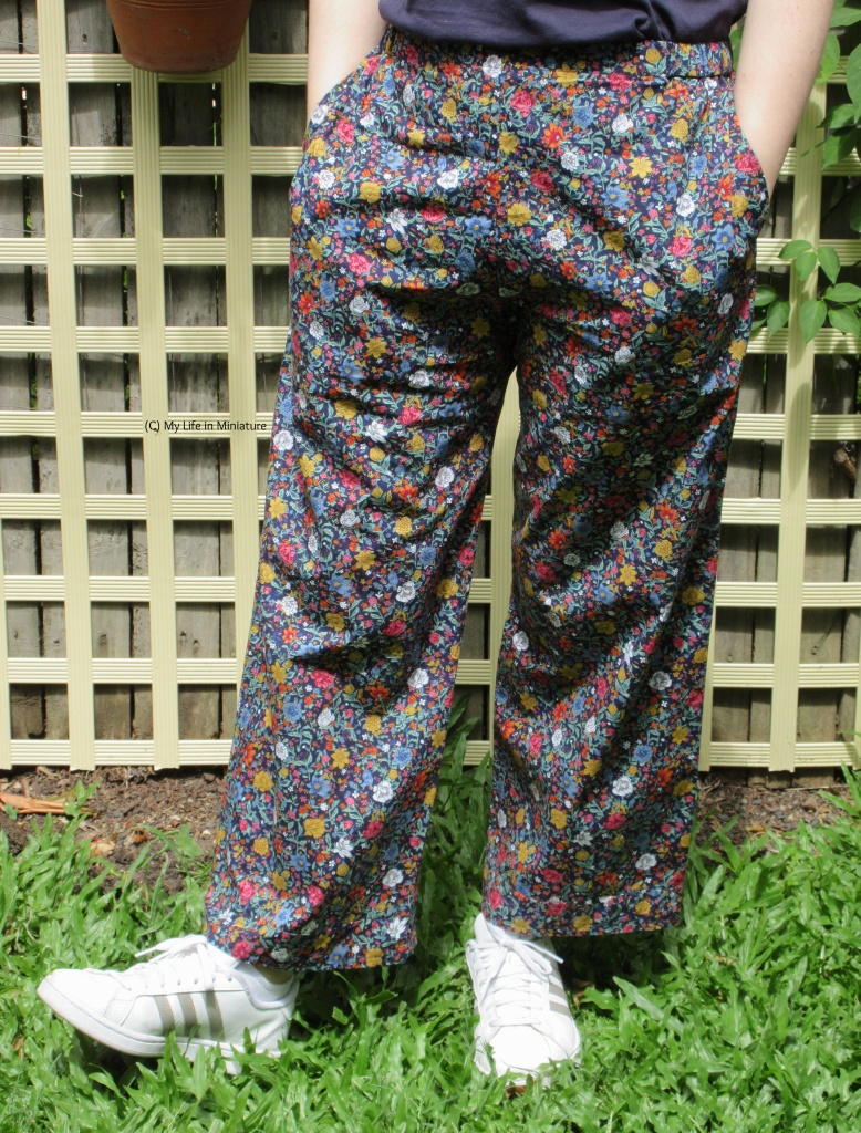 The author wears the floral pants, hands in pockets, and white shoes. She is outside, standing against a fence.