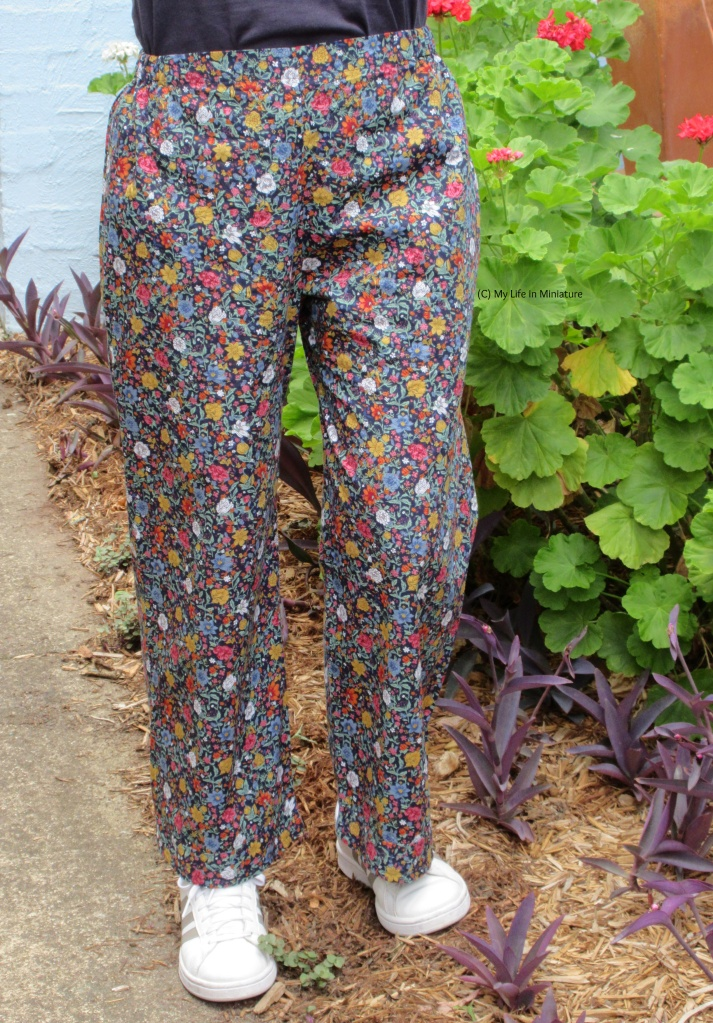 The author wears the floral pants and white shoes. She is outside, standing with a very large geranium plant in the background.
