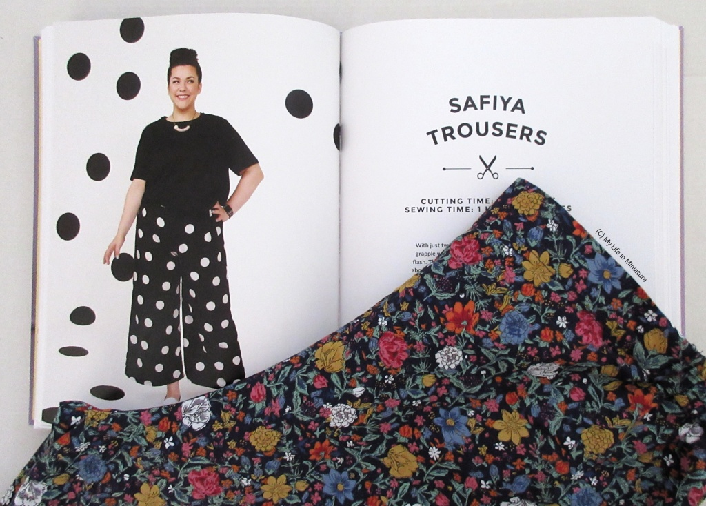The floral pants are laid over an open book. The book is open to a double-page spread with an image of a model wearing wide-legged pants and 'Safiya Trousers'  written on the other page.