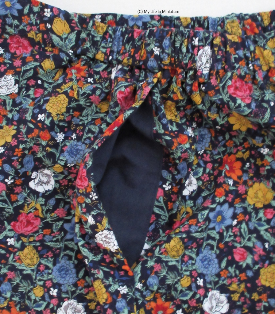 The floral pants are on a white background. The side seam is positioned so that the plain navy inside of the pocket is visible.