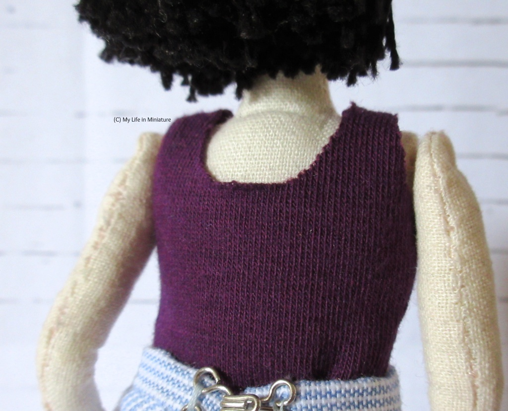 Back view of Tiffany's torso, showing the rounded back neck edge of the purple top.