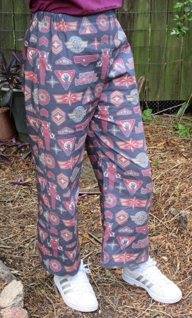 The author wears loose, elastic-waisted pants printed with a Captain Marvel-inspired design with white shoes. She stands outside on a garden pathway, one knee bent slightly.