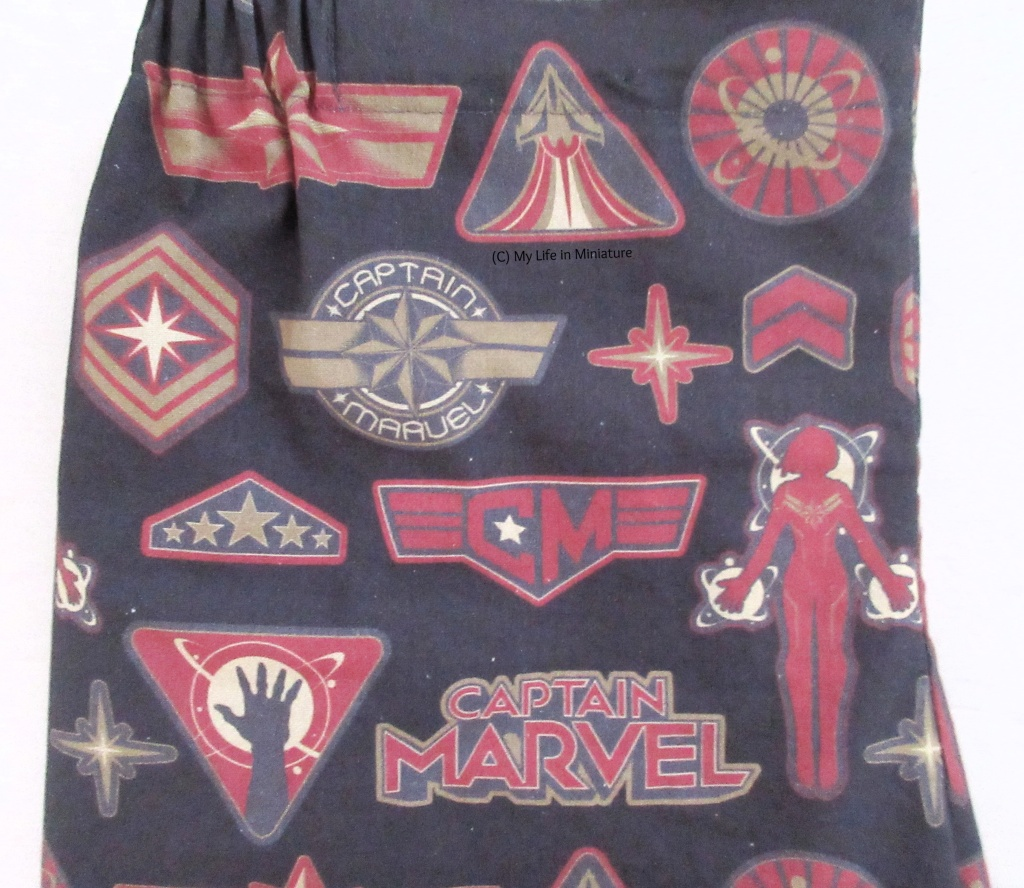 Close-up of the fabric. It has the movie logo and various symbols related to the MCU character, like her star and stripes, and a rocket ship taking off.