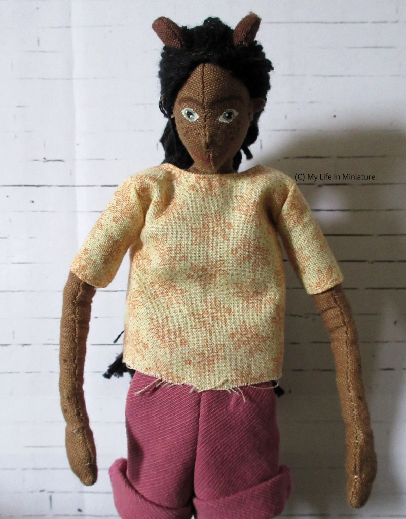 Petra wears an un-hemmed t-shirt in a cream fabric, printed with leafy designs in pale pink. She looks down at the shirt dubiously, arms by her sides.