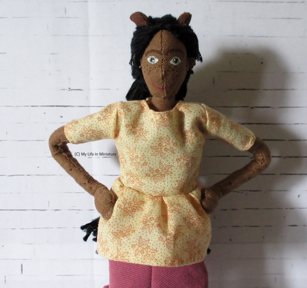 Petra wears a cream t-shirt with a gathered, peplum sort of hem. The gathers are at the waist, and the shirt has leafy designs printed on in pale pink. Her hands are on her hips and she smiles at the camera.