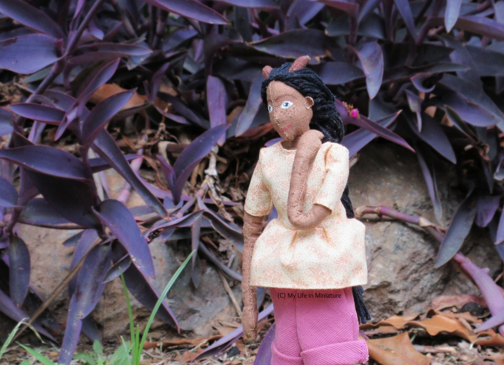 Petra stands outside, in front of a rock-bordered garden bed filled with a purple-leafed plant. She looks to the bottom-left, and has one hand on her shoulder. She wears the gathered cream t-shirt and pink corduroy shorts.