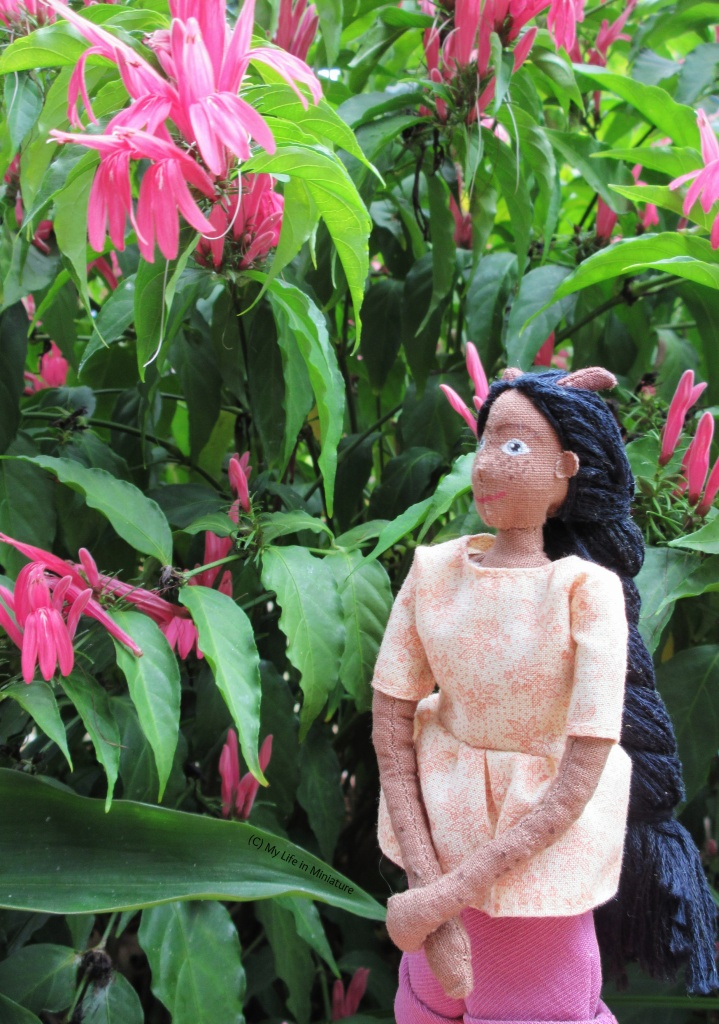 Petra stands outside against a pink flowering plant with long, thin leaves. She looks up at a cluster of pink flowers, hands clasped in front of her. She wears the cream gathered t-shirt.