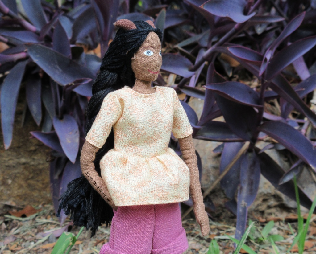 Petra stands outside, in front of a rock-bordered garden bed filled with a purple-leafed plant. She looks to the right, with one hand in her pocket. She wears the cream gathered t-shirt and pink corduroy shorts.