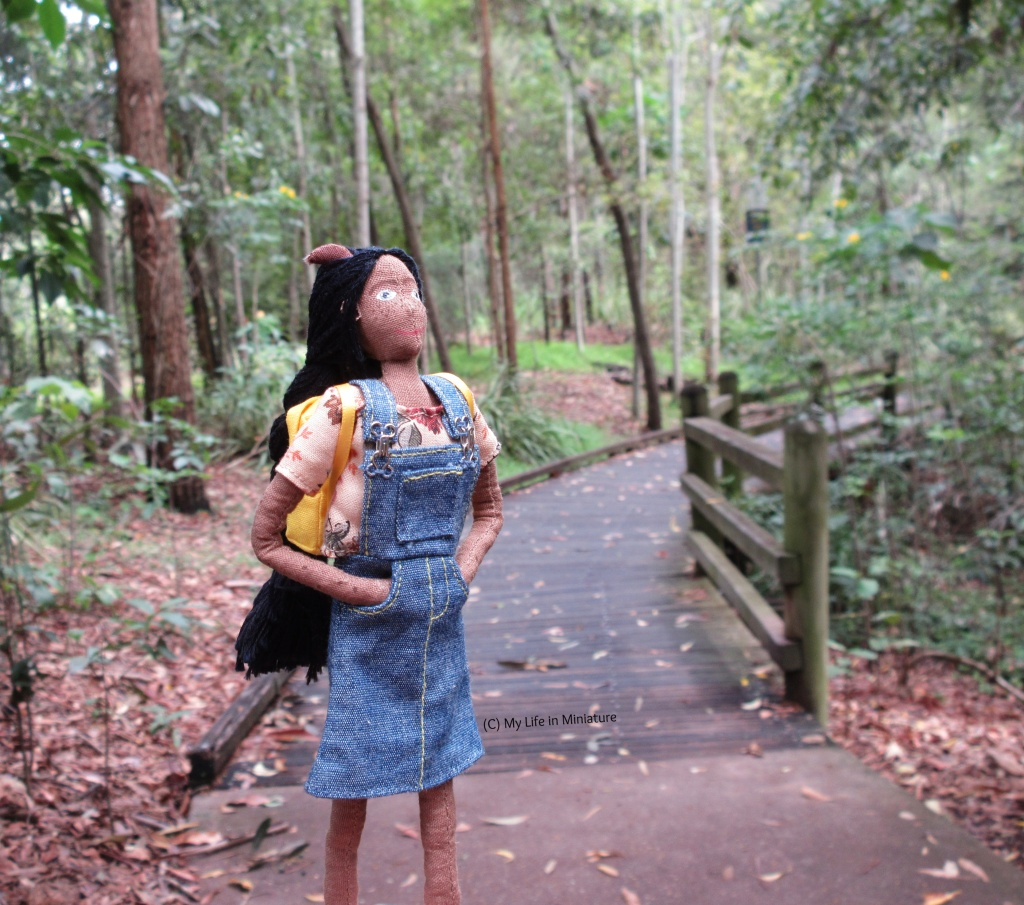 Petra stands on a path that curves away in the distance into a small forest. She looks up beyond the frame at the canopy. She wears her denim pinafore and a cream floral t-shirt and has her yellow backpack on.