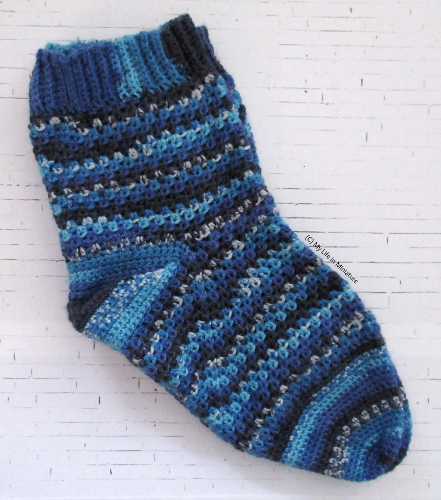 A pair of crocheted socks is laid flat on a white brick background. The socks are various shades of blue, with sections of speckled colour. The leg and foot sections are in a granny square-esque stitch, while the heel and toe are solid double crochet.