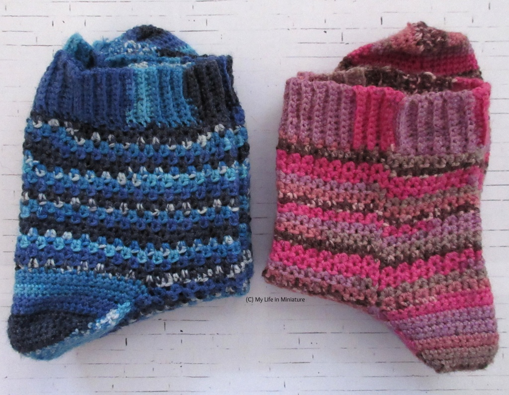 Two pairs of crocheted socks sit folded on a white brick background. The pair on the left are various shades of blue, with sections of speckled colour. The pair on the right are shades of pink, pale purple, grey, and speckled brown.