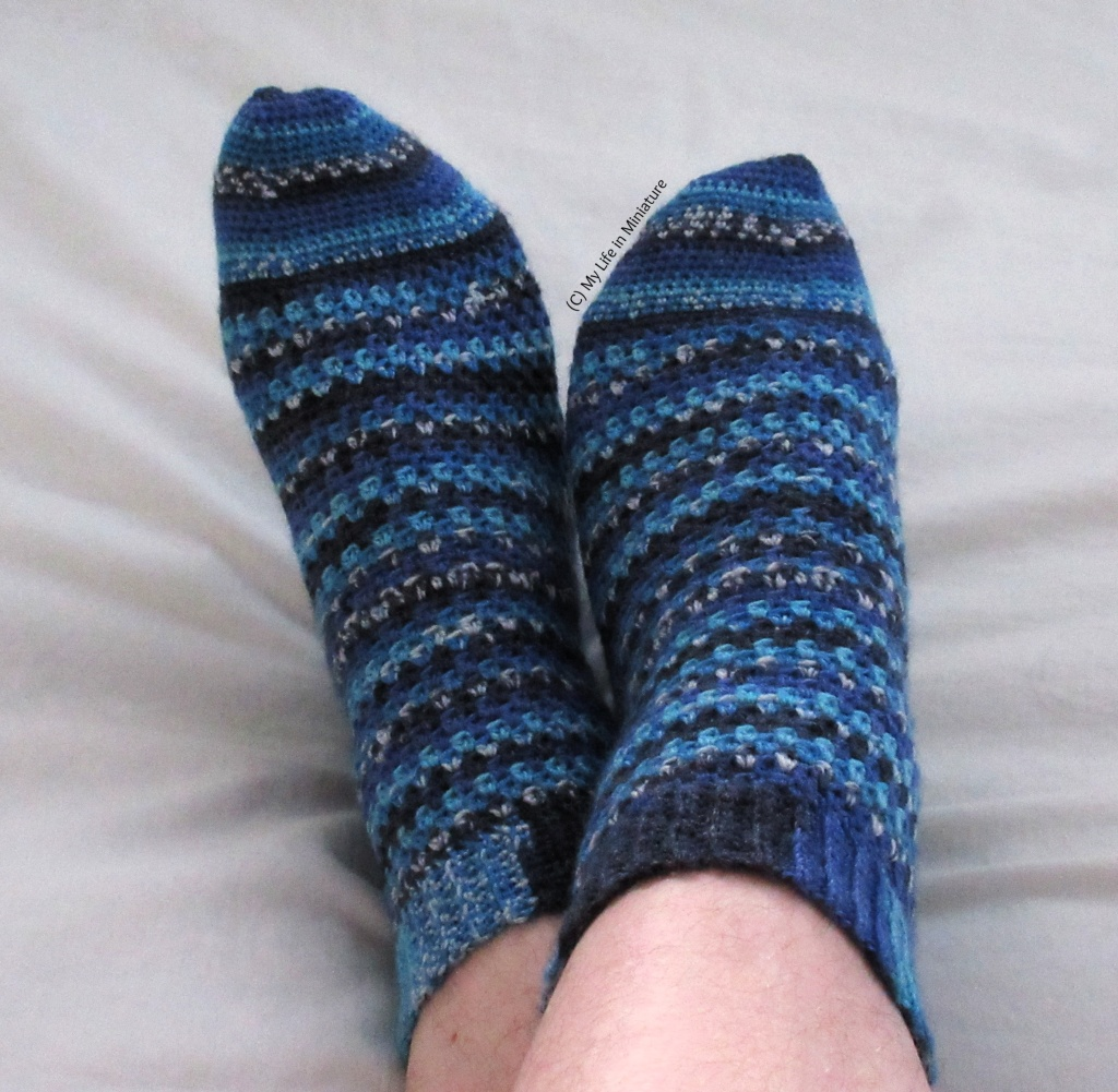 The author wears a pair of crocheted socks on a pale grey fabric background. The socks are various shades of blue, with sections of speckled colour. Her feet are crossed over each other.