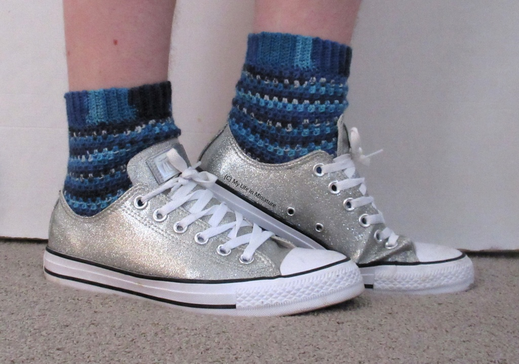 The author wears a pair of crocheted socks and silver sparkly Converse shoes against a white background. The socks are various shades of blue, with sections of speckled colour. Her feet are sideways, pointing to the right, and her back heel is raised.