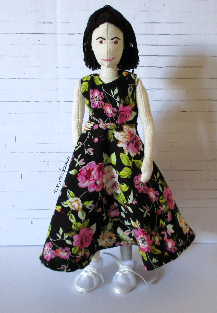 Tiffany stands in front of a white brick background. She wears an ankle-length sleeveless dress with a circular skirt and V-neck. It is black with pink and orange flowers on, and green leaves.