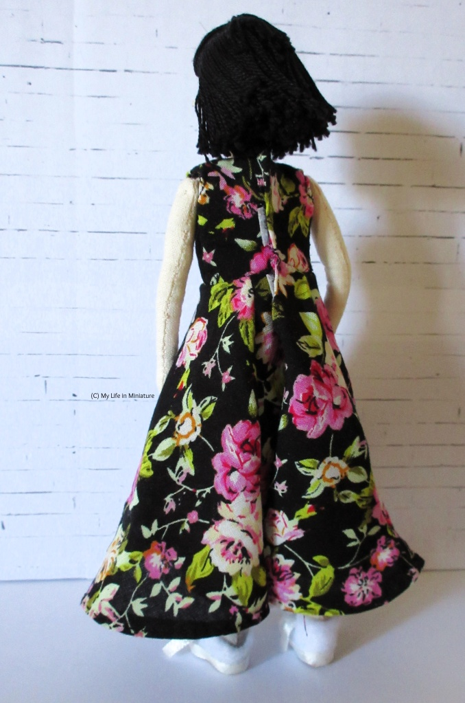 Tiffany faces away from the camera, wearing the ankle-length floral dress. The back of the dress is visible, and a Velcro fastening peeks out from the fabric overlap at the back of the torso.
