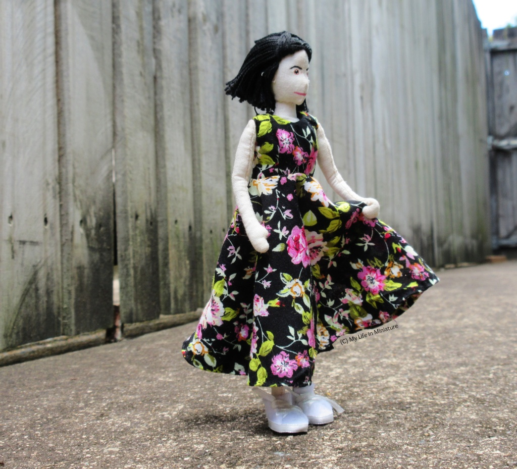 Tiffany stands outside, against a wooden fence, wearing the ankle-length floral dress and white runners. She holds the skirt in one hand and is turning to the right, as if she's about to twirl.