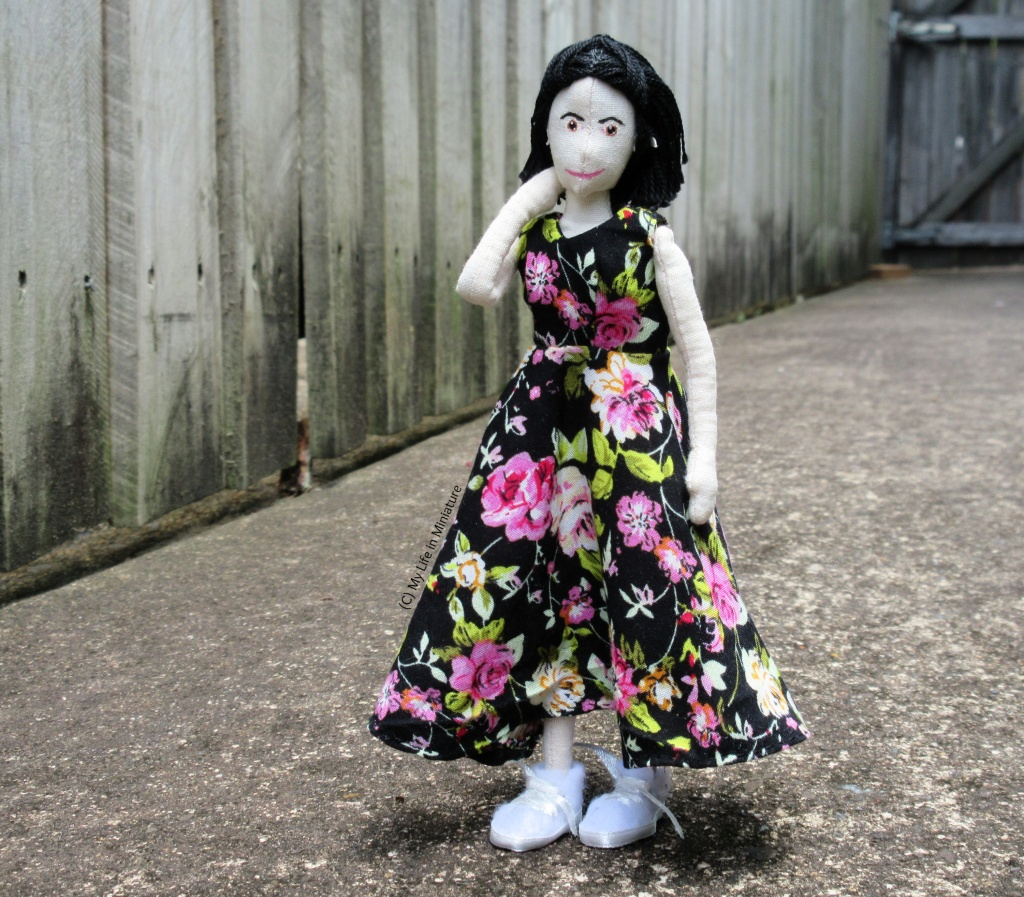 Tiffany stands outside, against a wooden fence, wearing the ankle-length floral dress and white runners. She looks at the camera with one hand tucking hair behind her ear.