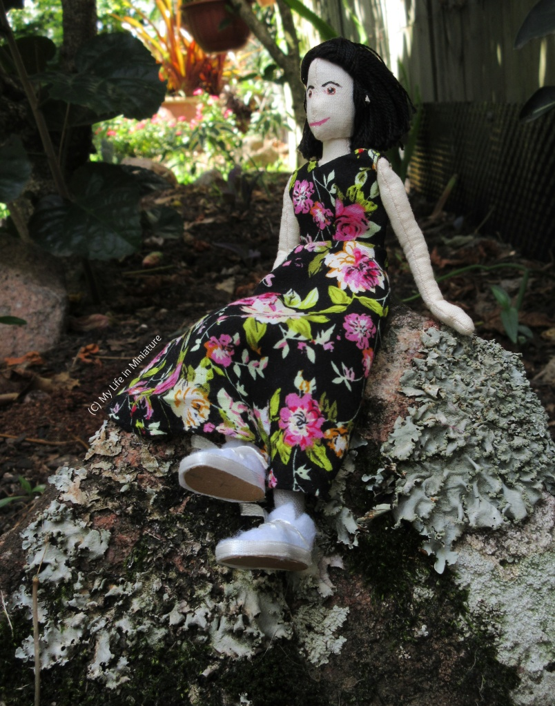 Tiffany sits on a rock covered in moss and a coral-like fungi. (I don't really know what it is.) She wears the ankle-length floral dress with white runners, and is sitting on it like it's a comfortable stool. She looks to the left.