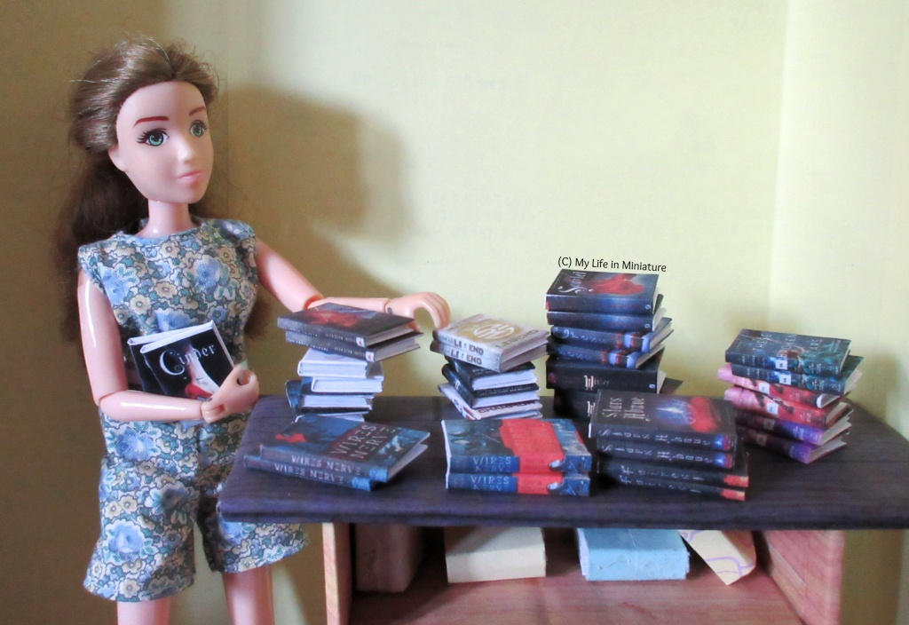 Sarah stands beside the stand-in front counter of The Palace Library. She is placing two books onto their series pile, and holds two more waiting to get sorted. The other books are sorted into piles by series.
