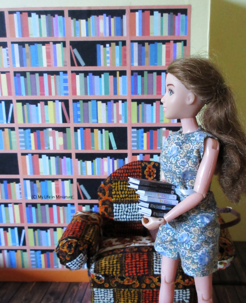 Sarah is walking towards one of The Palace Library's bookshelves, carrying an armful of books to shelve. A brightly coloured/patterned armchair is positioned in front of the shelves, and Sarah walks around it.