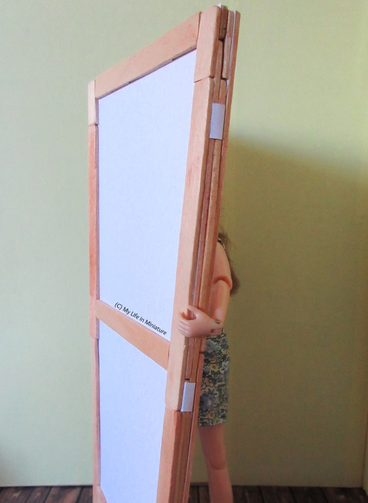 Sarah holds both room divider panels against a yellow background. The panels are folded so they are flush, and the white paper hinges that make that possible are in the foreground.