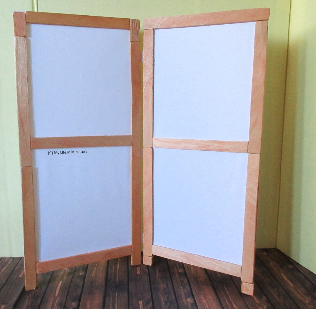 A white room divider stands against a yellow wall. Its frame is a light brown wood, and there are two connected panels that stand at a slight acute angle.