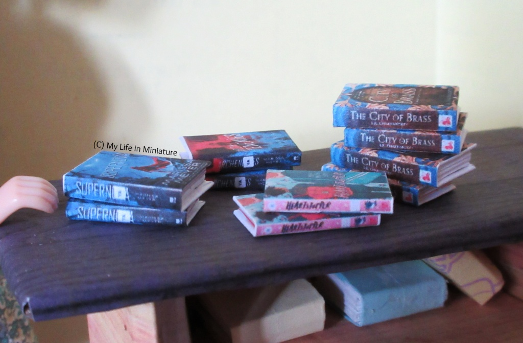 Several stacks of books are on the makeshift counter of The Palace Library, spines towards the camera. Three of the stacks have two books, and the one on the far right has four.
