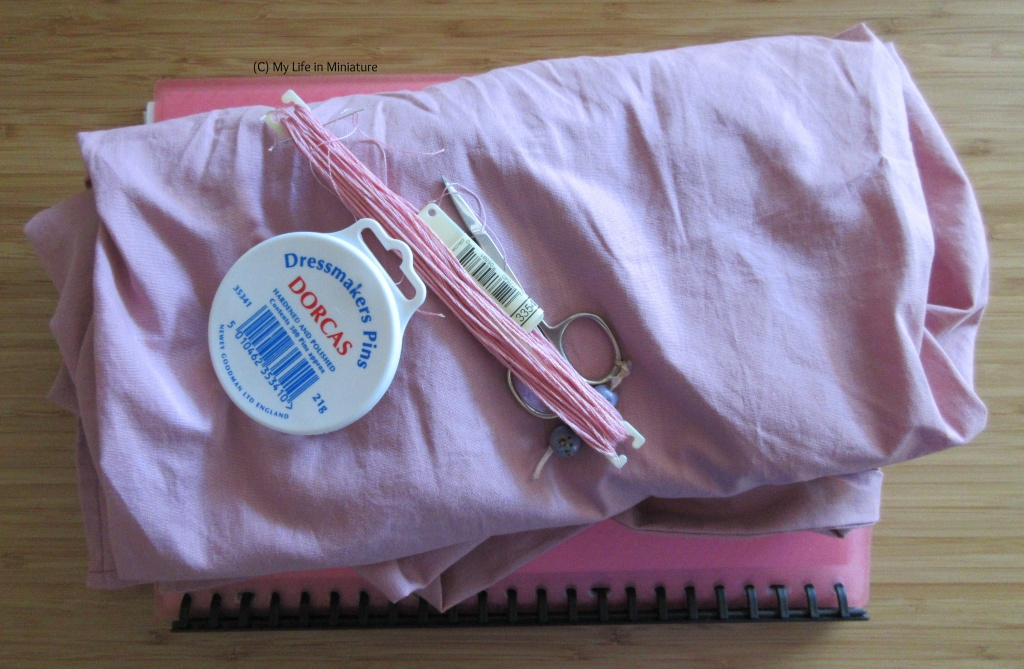 A pile of dusky pink fabric sits on a wood tabletop. On the fabric is a pin tin, a skein of matching embroidery thread, and a pair of embroidery scissors.