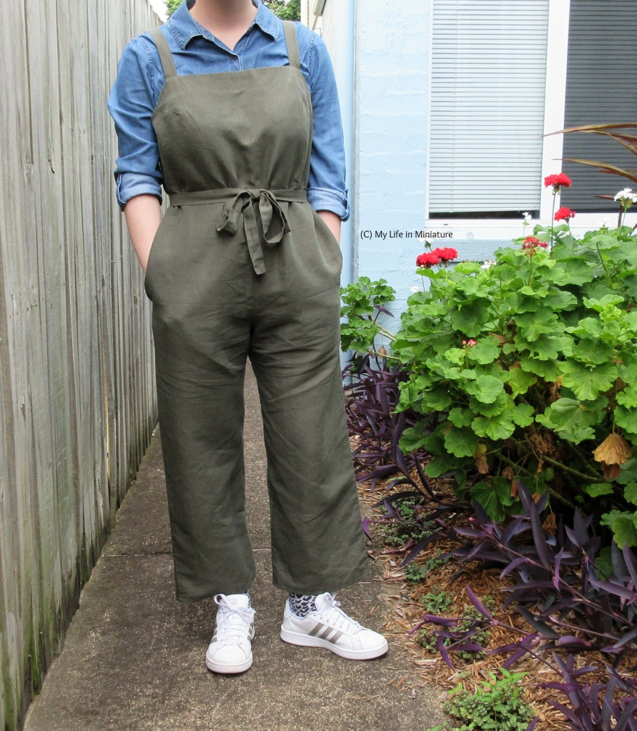 The author wears a pair of khaki green dungarees over a chambray shirt with white shoes. She has her hands in her pockets, and the dungarees have a waistband tied in a bow. She stands outside, on a concrete path beside a garden bed.