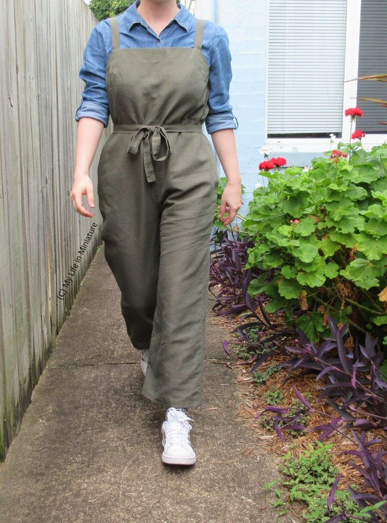 The author walks towards the camera, wearing the dungarees over a chambray shirt with white shoes. Her arms are at her sides, and she is on a pat next to a garden bed.