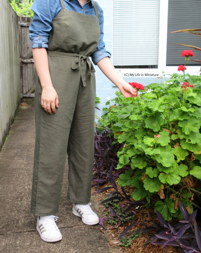 The author stands on the garden path, holding the stem of a red flower in the garden bed. She wears the dungarees over a chambray shirt with white shoes. Her other hand hangs at her side.