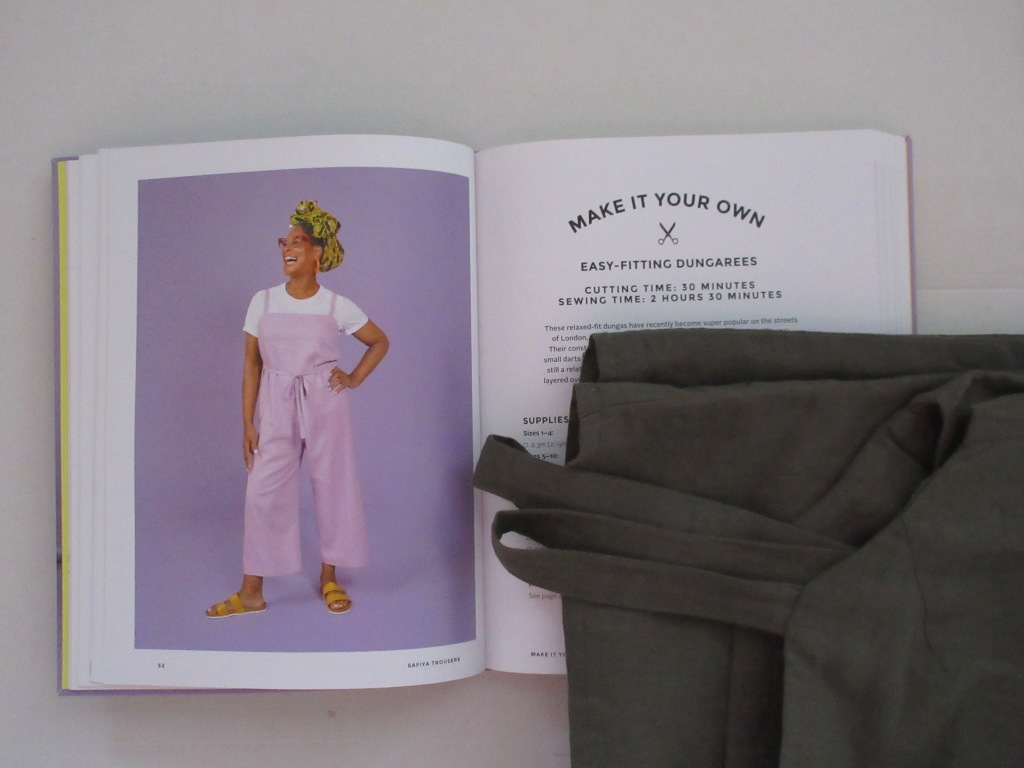 The dungarees lie folded next to an open book on a white background. The book is open to a double page with an image of a woman wearing purple dungarees and the first page of instructions for making the dungarees.