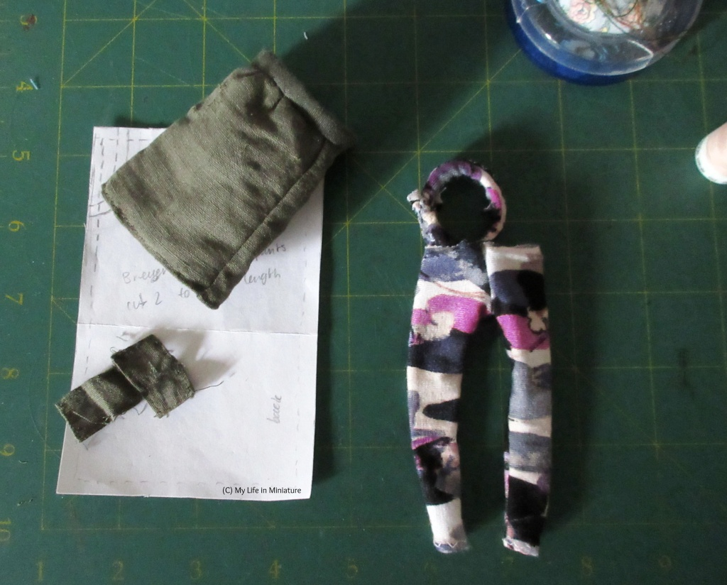 A doll-sized khaki skirt and a pair of doll-sized leggings sit on a green cutting mat. The leggings have a waistband that is not attached to the legs.