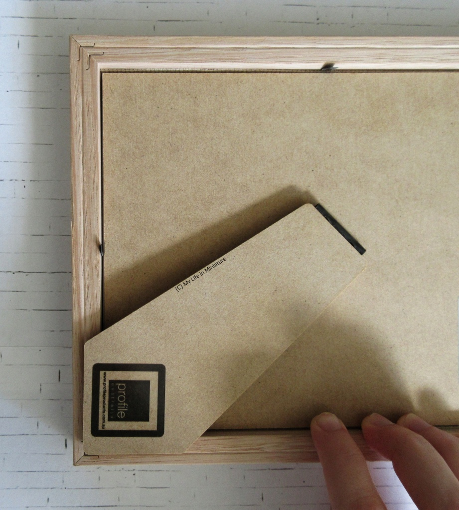 The back of a picture frame is on a white brick background. The author's fingers are visible, attaching the bard back into place.