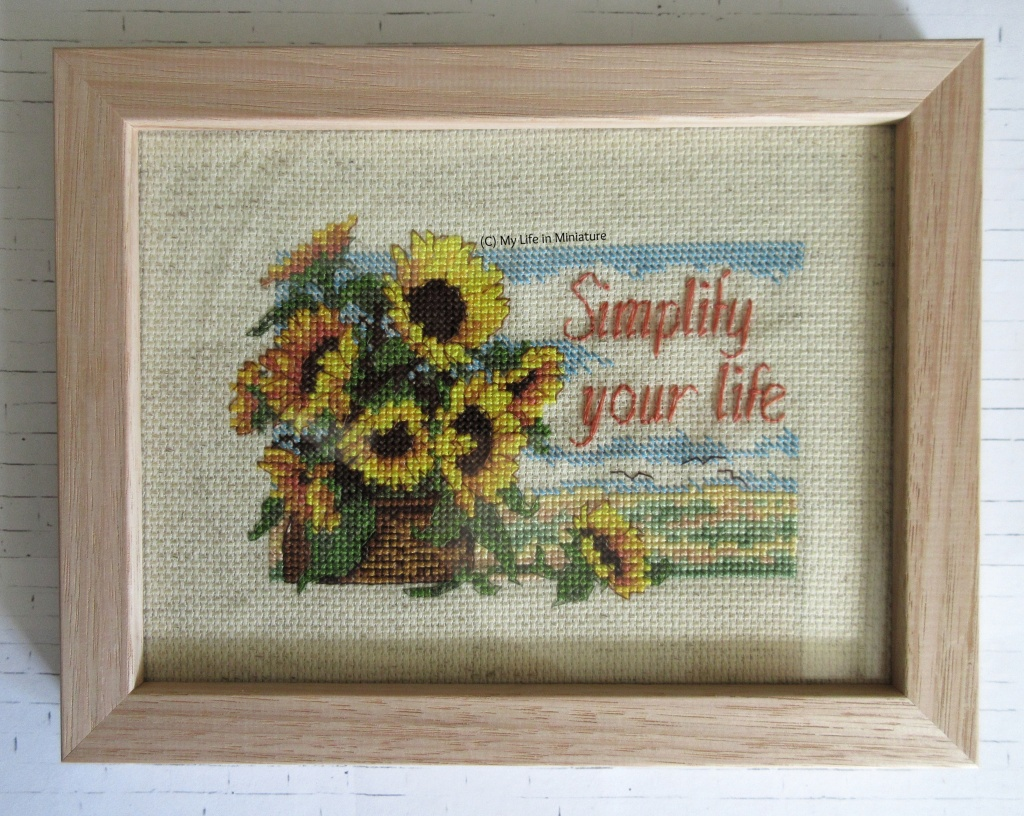 A light wood frame, with glass, sits on a white brick background. In it is a cross-stitching of nine sunflowers in a basket against a field and sky. Text to the right of the sunflowers says 'Simplify your life'.